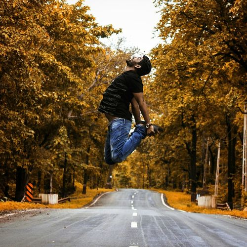 Man Jumping On Road Amidst Trees During Autumn