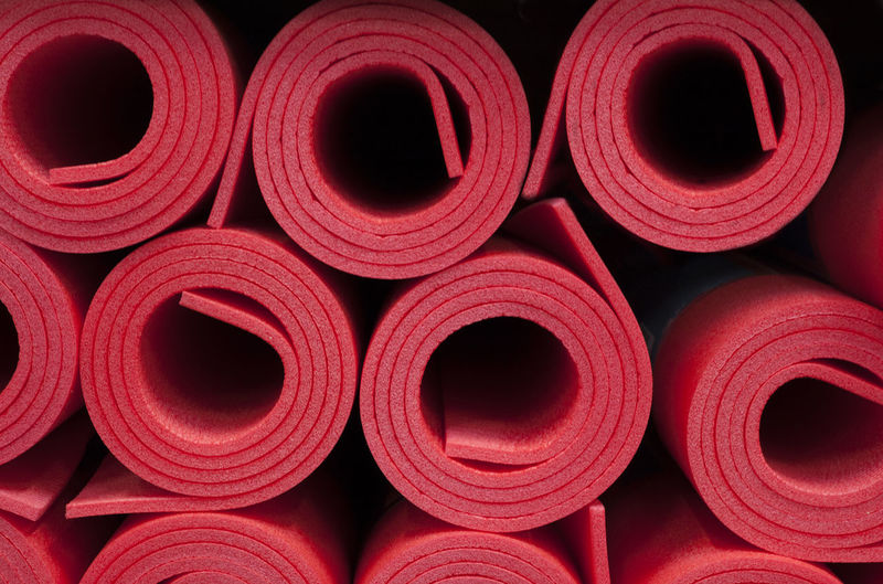 Lot of rolled up red foam fitness mats background. Travel and sport Arrangement Backgrounds Close-up Design Full Frame Group Of Objects Indoors  Industry Large Group Of Objects No People Pattern Red Repetition Rolled Up Shape Side By Side Spool Stack Still Life Thread