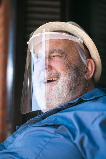 Elderly man smiling under a protective visor