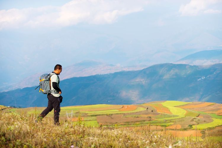 Hiker Walking On Field Against Mountain Range