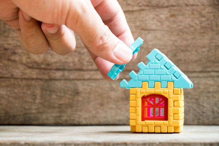 Man hold piece of puzzle to complete the home model object on wood background (Concept of dream home, mortgage investment, family fulfillment) Business Construction Dream FULFILL Family Home Land Life Loan  Wood Block Building Complete Connect Development Hand House Investment Jigsaw  Mortgage Part Piece Property Success Toy