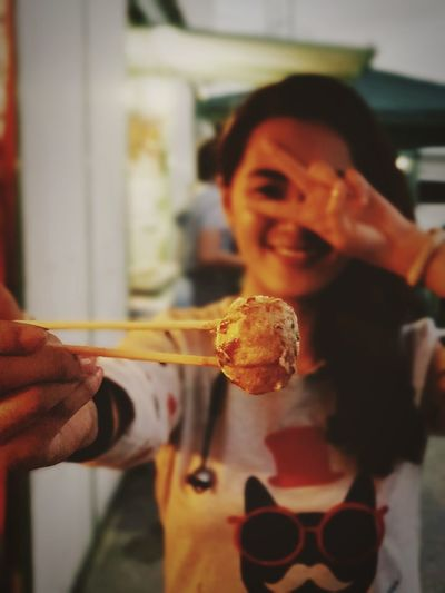 Close-up of smiling woman holding meatballs with chopsticks