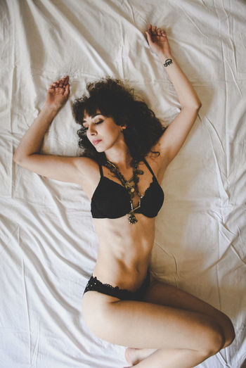 Directly above shot of seductive young woman lying on bed at home