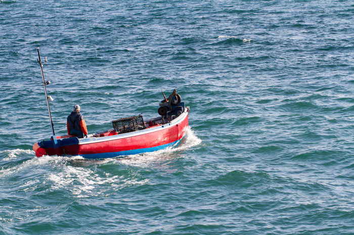 A fisherman heading out to sea in a small, traditional Cornish fishing boat off the coast of Cornwall, UK. Fisherman Fishing Boat Fishing Cornwall Cornwall Uk Cornwall Life Traditional Small Sea Ocean Waves Choppy Waters Choppy Coast Coastal Sailing Sailing Away Morning Alone Solitary Industry Fishing Industry Local Local Culture Uk Business Stories