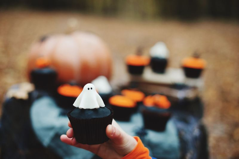 Cropped hand of child holding cupcake during halloween celebration
