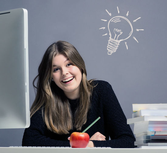 Portrait Of Smiling Young Woman Sitting Studying At Table