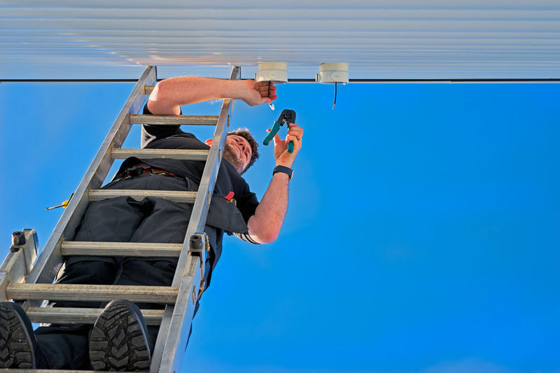 Man On A Ladder Crimping An Ethernet Cable Blue Blue Sky Boots Cable Cat5 Clear Sky Concentration Crimping Tool Day Ethernet Ladder Ladder On The Wall Low Angle View Man Man On Ladder Outdoors Screwdriver Technology Tool Tools Of The Trade Watch White Wall Workman