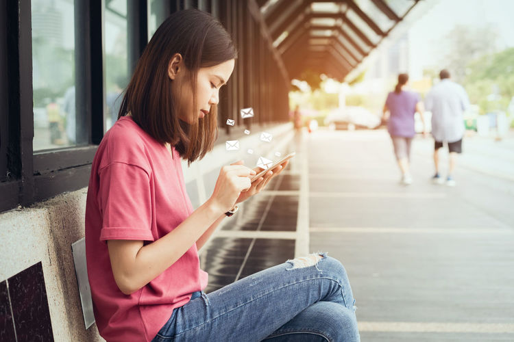 Woman using mobile phone with email icons while sitting on bench