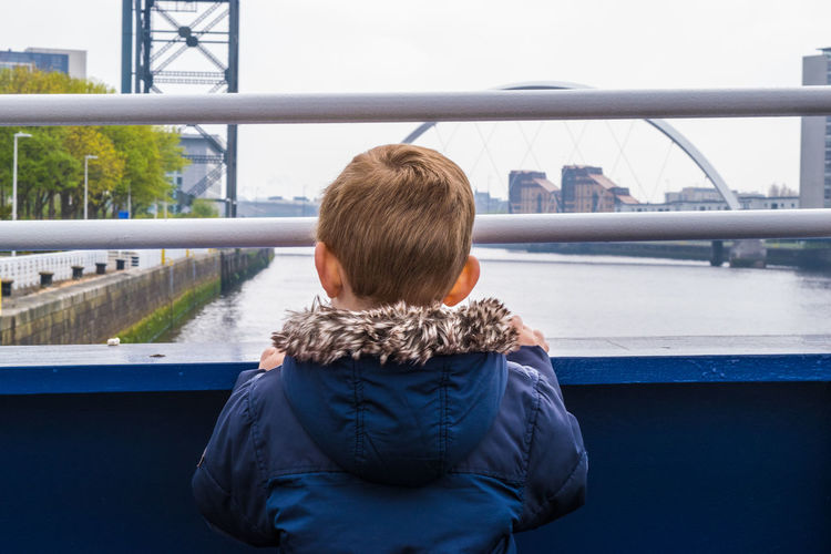 Rear view of boy standing on bridge over river