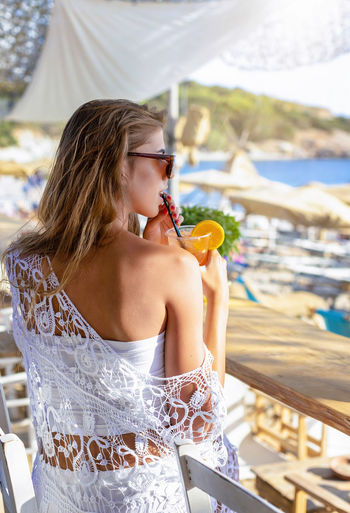 Attractive, blonde woman enjoys a drink at a beach bar during her summer vacation Food And Drink Focus On Foreground Holding Leisure Activity Women Real People Sitting Fashion Hairstyle Beautiful Woman Outdoors Young Women Young Adult Lifestyles Beach Summer Bar Sexygirl Cocktail Aperitif Vacations Holiday Blonde Back Day