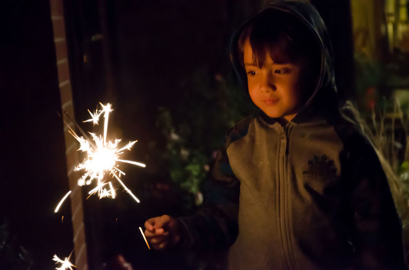 Close-up of cute boy holding sparkler at night