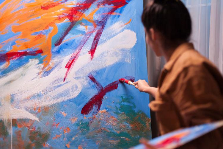 Full length of man holding painting