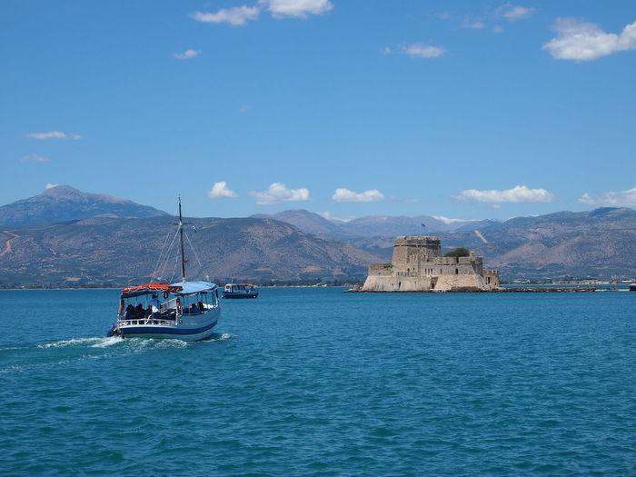 Ferry Sailing Towards Bourtzi Sea Castle In Nafplio Against Sky