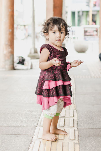 Full length portrait of girl dripping saliva while standing outside house