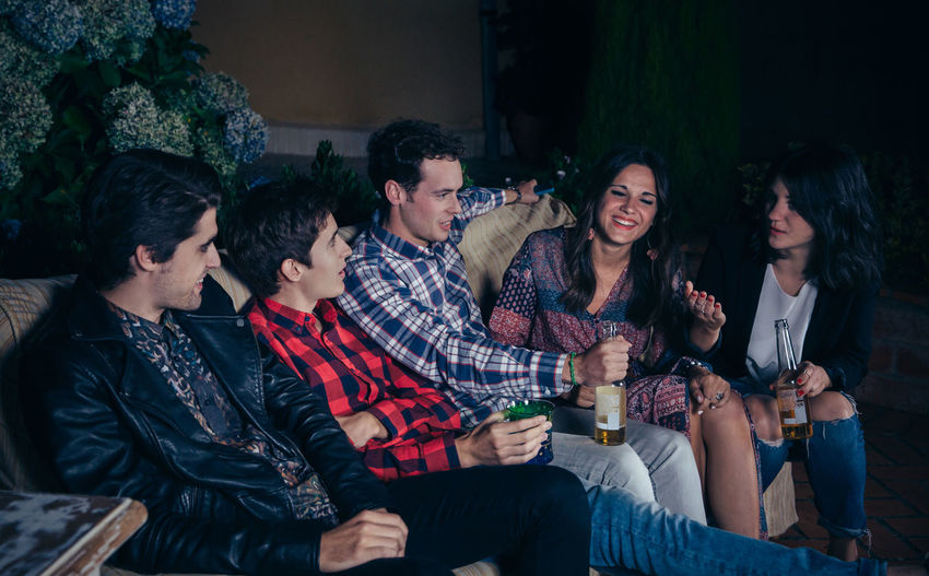 Friends Talking While Sitting On Sofa At Patio During Night