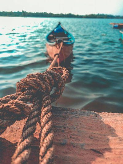 Boat tied with rope on retaining wall