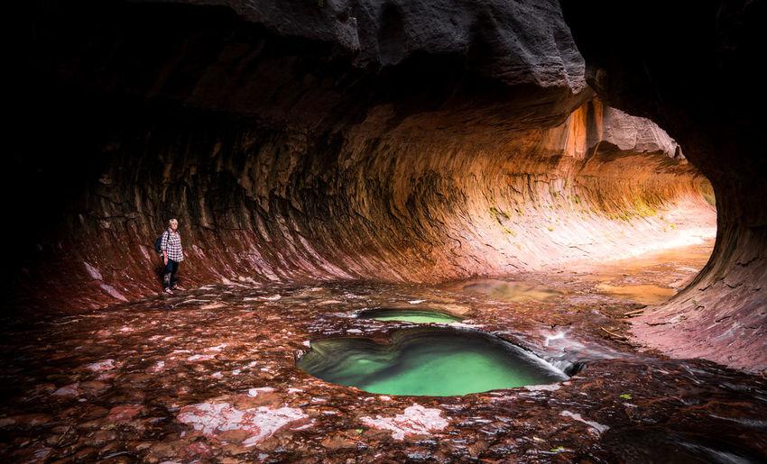 Senior woman standing inside cave