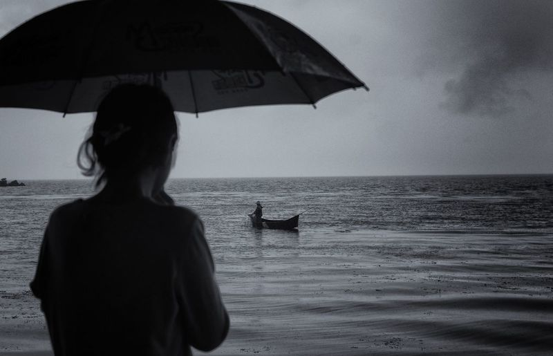 Rear View Of Woman Holding Umbrella Standing Against Sea And Sky