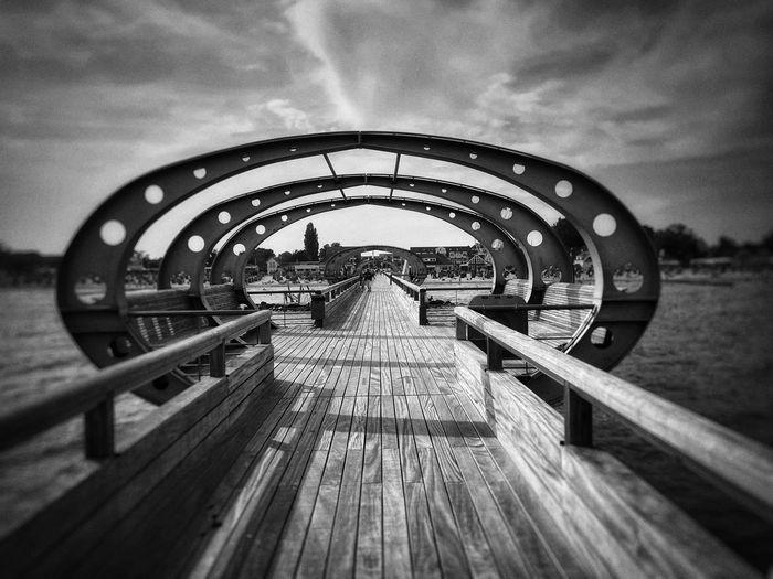 View of pier on footbridge against sky