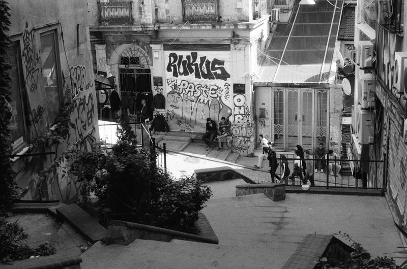 A back alley scene in Istanbul Turkey of everyday life with teenagers. - Photos taken on 35mm film with Canon AE-1 Program analog camera. Streetwise Photography Streetphotography Street Analogue Photography Analog 35mm Film Film Photography Canon AE-1 Canon Canon AE-1 Program  Black And White Blackandwhite Black & White The Week on EyeEm Best Of EyeEm My Best Photo Fomapan Fomapan400 Architecture Incidental People Group Of People Building Exterior The Art Of Street Photography
