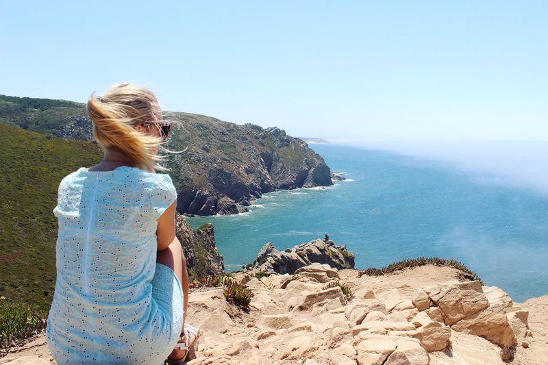 EyeEmNewHere Sea One Person Rock - Object Real People Standing Clear Sky Leisure Activity Water Day Rear View Nature Horizon Over Water Casual Clothing Lifestyles Outdoors Scenics Blue Beauty In Nature Sky Women
