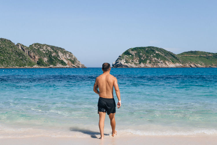 Sea Shirtless Sky One Person Beach Land Water Standing Beauty In Nature Leisure Activity Rear View Lifestyles Nature Real People Young Adult Day Clear Sky Vacations Young Men Outdoors Shorts Ankle Deep In Water