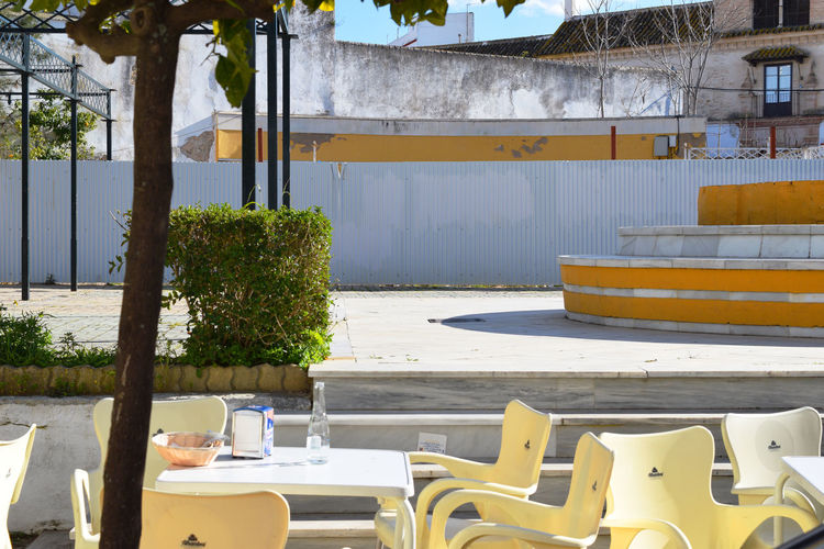 small square in the Andalusian town Carmona with the bright midday light Africa Andalusia Architecture Bench Bright Light Built Structure City Day Light And Shadow Outdoors Seat Square Table Tree