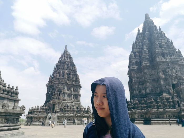 Woman in hooded shirt against old temples