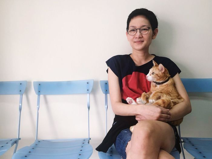 Asian  Care Love Cafe Pet Animal Hospital Cat Doctor  Veterinary One Person Glasses Real People Eyeglasses  Front View Women Domestic Animals Looking At Camera Adult Domestic Pets Three Quarter Length Portrait Emotion Mammal Sitting Smiling One Animal Hairstyle Positive Emotion