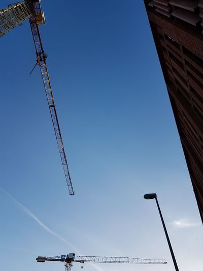 Architecture Blue Building Exterior Built Structure Clear Sky Construction Equipment Construction Industry Construction Site Crane - Construction Machinery Day Development Industry Low Angle View Machinery Metal Nature No People Outdoors Sky Tall - High Vapor Trail