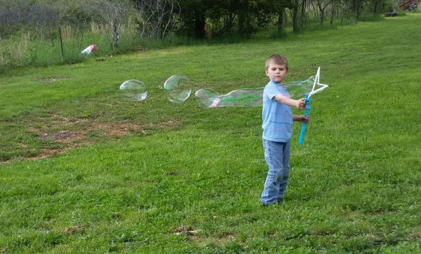 Full length of boy making bubbles on grassy land