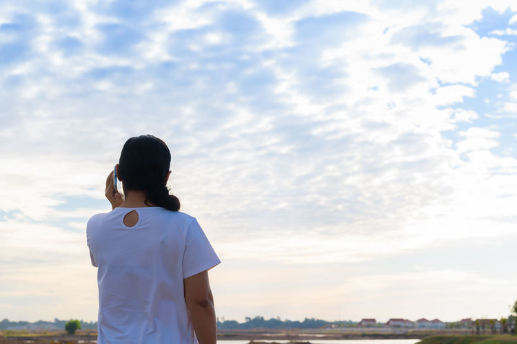 Rear view of woman answering smart phone while standing against cloudy sky