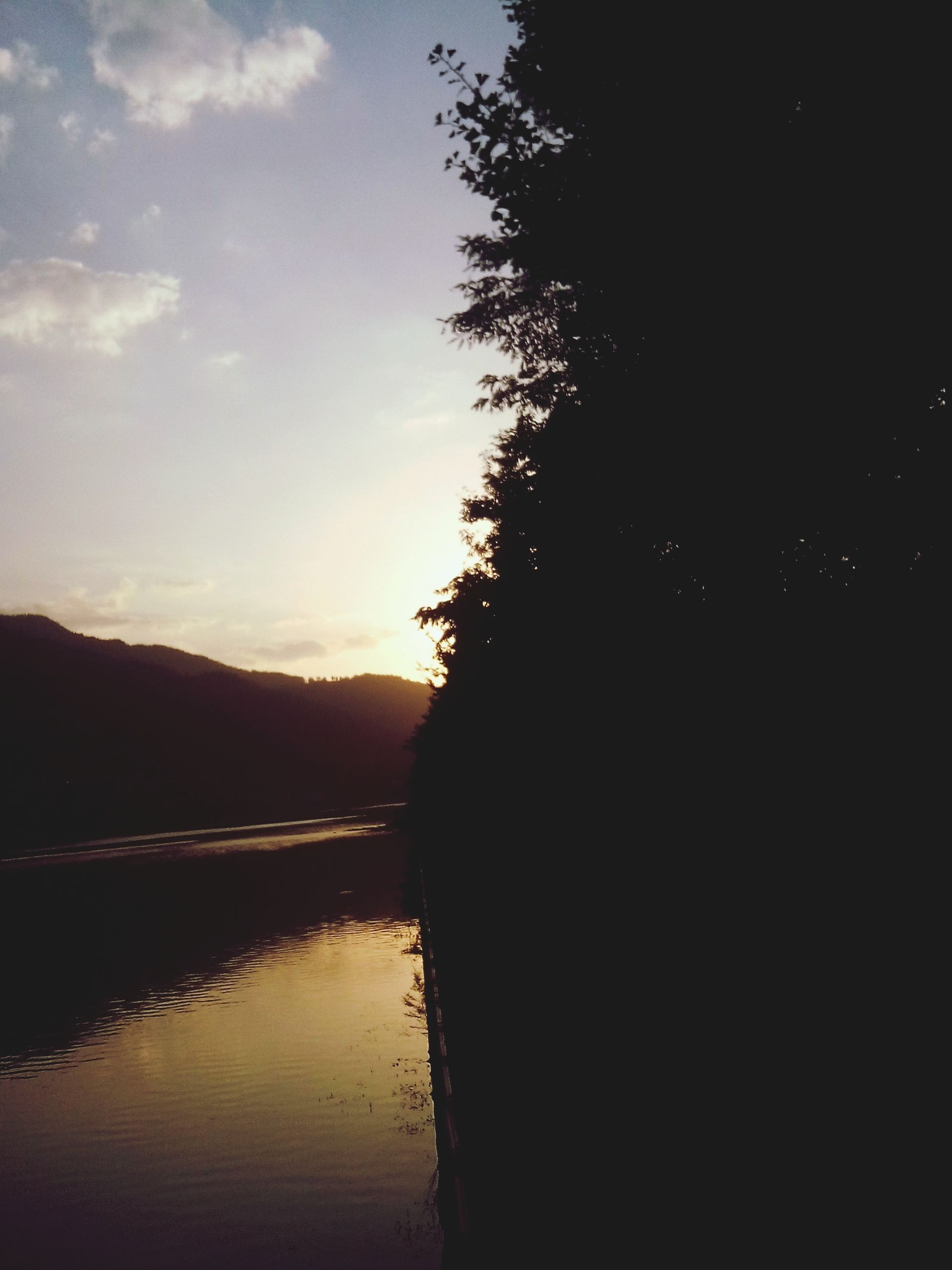 water, silhouette, tranquil scene, tranquility, sunset, scenics, reflection, lake, sky, beauty in nature, nature, river, tree, idyllic, mountain, calm, dusk, waterfront, outdoors, landscape