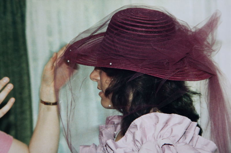 Cropped hands adjusting hat of young woman