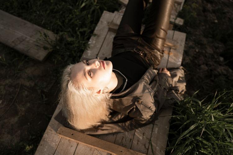 High angle view of woman lying on wood