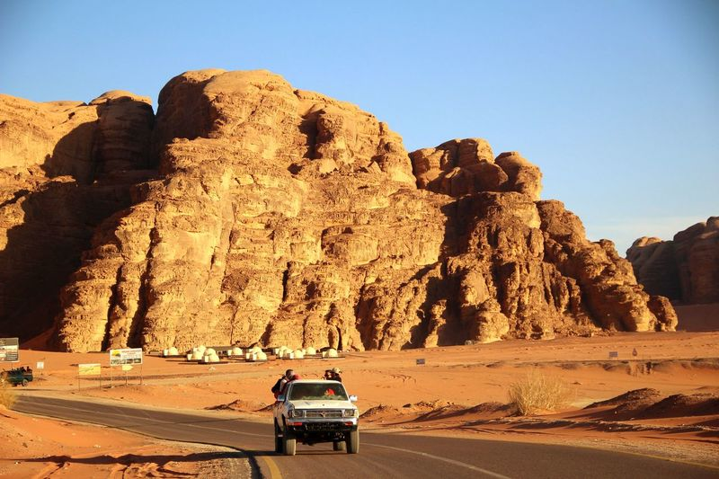 Car on rock formation in desert against sky