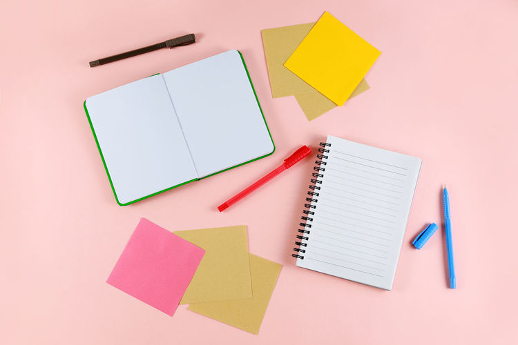 Directly above shot of diary and pens on pink background