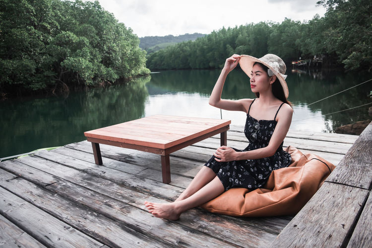 Full length of woman sitting by lake