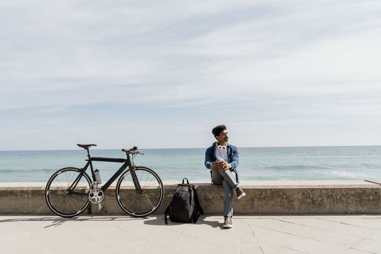 Man with bicycle by sea against sky