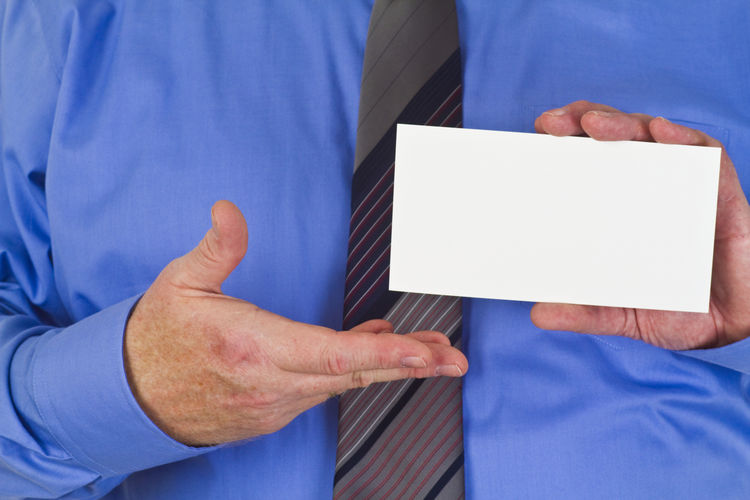 Midsection Of Businessman Holding Card
