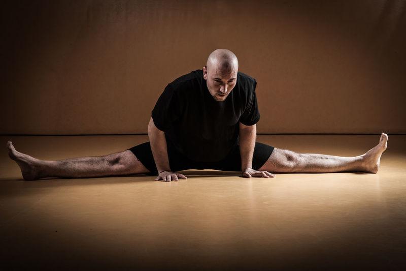 Kickboxer stretching in gym dojo.
