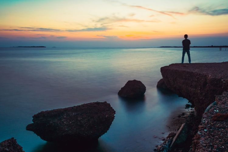 Rear View Of Silhouette Man Standing On Cliff By Sea Against Dramatic Sky During Sunset