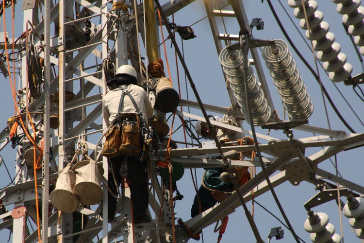 Maintenance engineers repairing electricity pylon