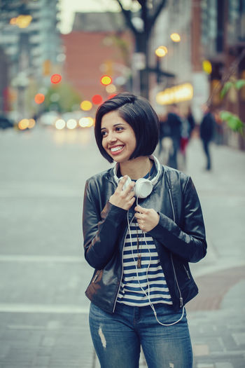 Smiling young woman standing on street