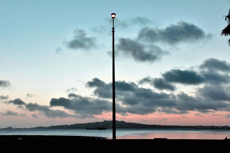 Street light on silhouette beach against sky during sunset