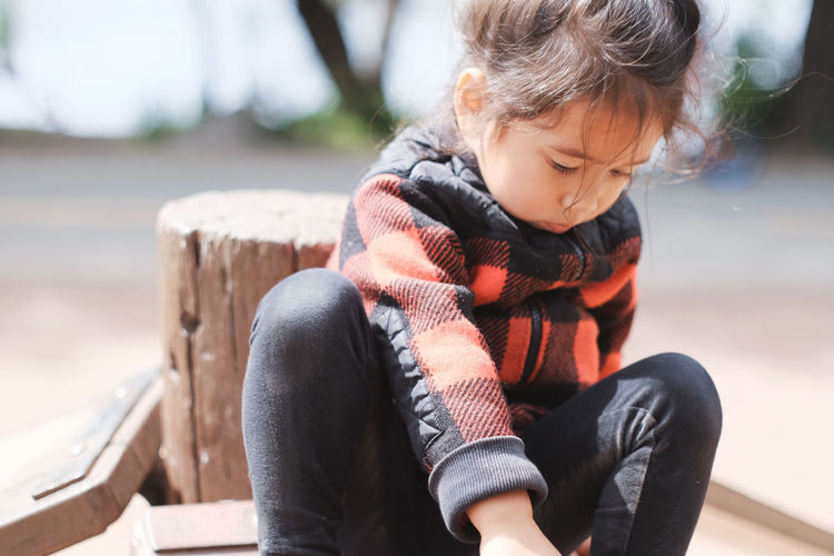 Cute Little Girl Sitting On Wood On Sunny Day