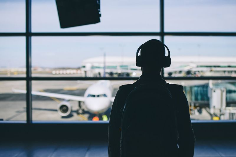 Passenger with headphones. Young man walking through airport terminal to airplane. Airport Airport Terminal Departure Travel Men People Young Men Air Vehicle Transportation Window Airplane Indoors  Airport Runway Journey Headphones Listening Music Sound Relaxing Looking Through Window Leaving Silhouette Passenger Trip Vacations