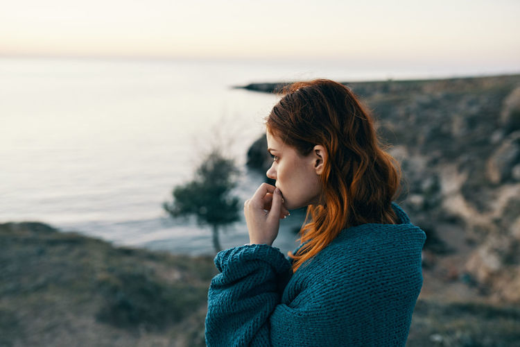 Young woman standing by sea against sky during sunset