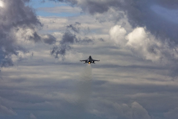 Low angle view of fighter airplane flying in cloudy sky
