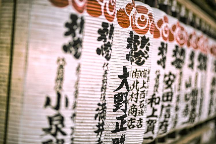 Close-up of text hanging on wall at temple
